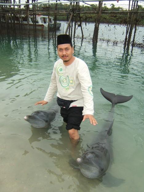 Aries pun tak mau kalah, nyemplung ke laut mendekat sang dolphin yang jinak,